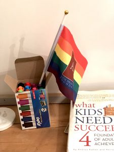 Markers, small pride flag and book in office