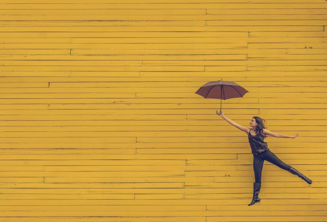 woman dancing with umbrella looks free