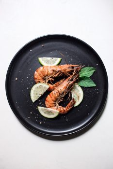 cooked shrimp on a black plate with garnishes