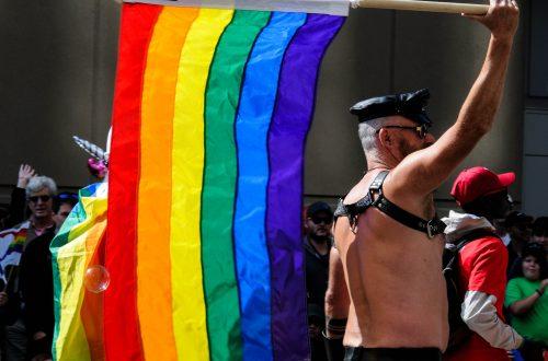 man waving flag in pride parade