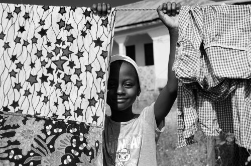 grayscale photo of boy in hat holding clothes hanger rope with clothes