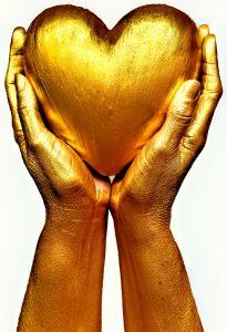 Gold hands holding grateful heart